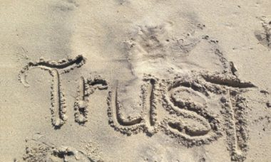 Trust in God written in the sand